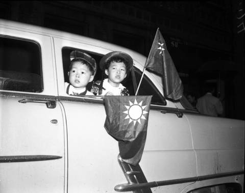 Henry Lee, 4, left, and Fay Lee, 5, look out the window while a downpour failed to halt the 1954 parade marking the 43rd anniversary of the founding of the Republic of China.