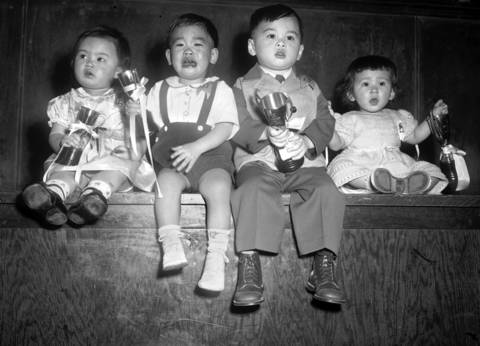 "Winners of the Chinatown baby contest in 1950 are, from left, Linda Wong, 15 months, second place; Chester Choi, 18 months, second place; Allen Eng, 2, first place; and Linda Mae Brunker, 16 months, first place. The winners pose for a portrait at the On Leong Merchant Association Building at 2216 S. Wentworth Ave., known as the ""Chinese City Hall"". The building is now the Pui Tak Center."