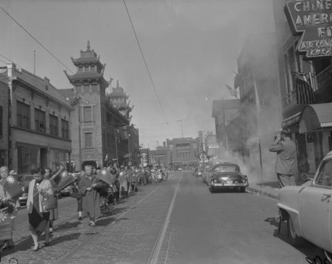 Chinese people parade on Wentworth Avenue in Chinatown to commemorate the 45th anniversary of the founding of the Republic of China in 1956. The smoke on the right is from firecrackers.