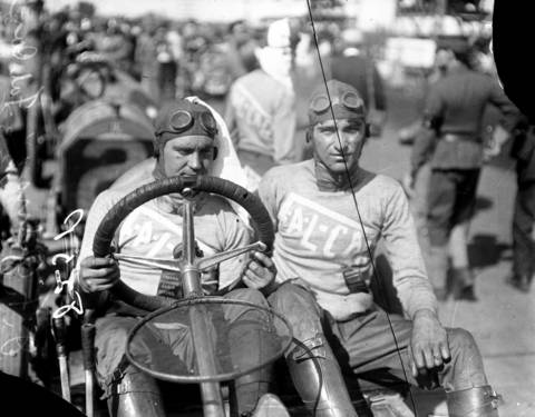 """J. F. Gelnaw, auto driver, at the Elgin National Road Races sitting next to his mechanic, circa 1910. Gelnaw and his mechanic were most likely driving a Fal-Car, according to their sweaters. Fal-Car's were manufactured between 1909 and 1914 and were known as """"A Car Without A Name"""", due to the fact that the manufacturers wanted the buyers to name the cars. The Elgin races were held from 1910 until 1920, with the exception of the World War I years. The track was a little over 8 miles."""