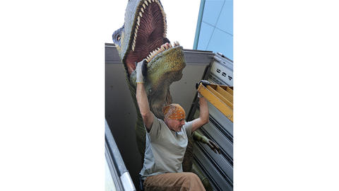 Scott Worth makes sure the dinosaur safely disembarks to be installed in the Virginia Living Museum's new show.