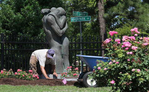 "For the bronze couple in Masaru Bando's sculpture, "" Due"", sometimes you just can't get a little privacy. Matthew Gobla is putting down mulch in preparation for today's unveiling of the sculpture, which Newport News Public Arts Foundation has dedicated to Carol Cap--."