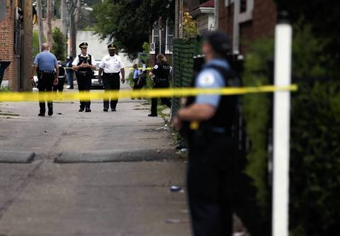 Chicago Police work the scene of a shooting involving a 16-year-old boy in the 8700 block of South Morgan Street in Chicago on July 5, 2014.