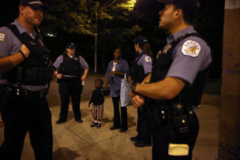 Officers on a foot patrol chat with residents at the scene where one victim was shot near the 600 block of North Ridgeway Avenue on July 3, 2014.