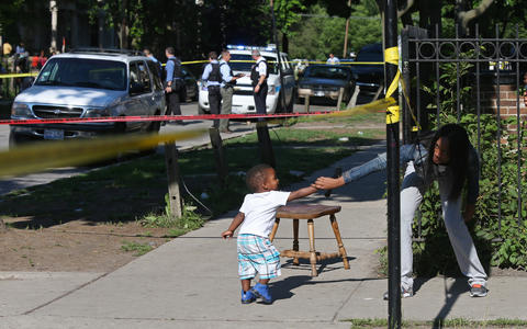 A woman grabs a child as he crosses police tape at the scene of a double-shooting in the 3800 block of West Monroe Street on July 3, 2014.
