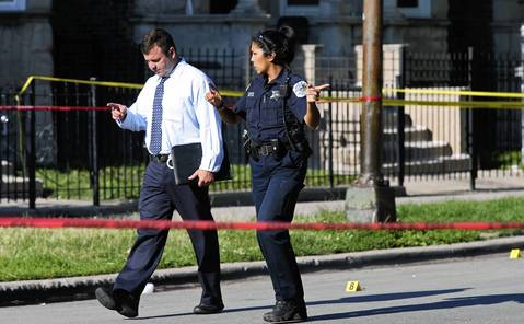 A Chicago police detective sergeant (left) and a forensics services officer investigate the scene of a double-shooting in the 3800 block of West Monroe Street on July 3, 2014.