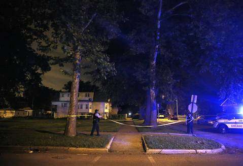Police mark a crime scene in the block of South Muskegon Avenue while searching for a gunman after police found three gunshot victims on July 7, 2014.