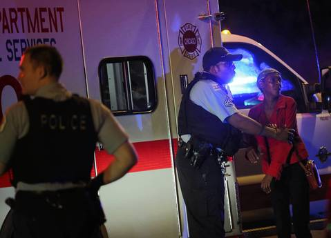 A police officer trie to calm a woman desperate for the identity of shooting victims in the 8400 block of South Loomis in Chicago on July 6, 2014.