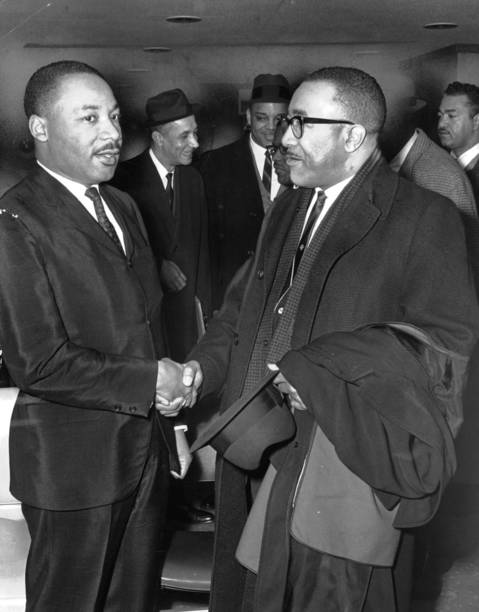 Martin Luther King Jr., left, greets the Rev. A.P. Jackson, of Liberty Baptist Church of Chicago, as King arrived at O'Hare International Airport. He was in Chicago for a speech in Orchestra Hall.