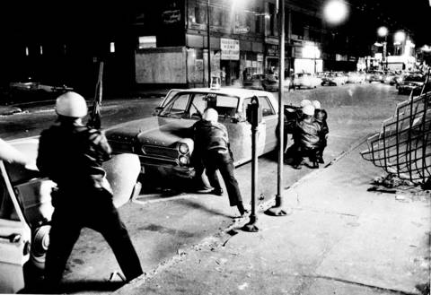 Chicago police, shown here with rifles, crouch behind a patrol car to take cover from gunfire during the riots that followed the assassination of Martin Luther King Jr. in 1968. Three hundred-fifty people were arrested for looting, and 162 buildings were destroyed by arson. Published accounts say nine to 11 people died in the riots.