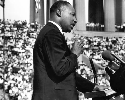 Martin Luther King Jr. addresses the crowd at the Illinois Rally for Civil Rights at Soldier Field in Chicago. King called for the strict enforcement of new civil rights legislation and a continued effort to end racial discrimination and poverty.