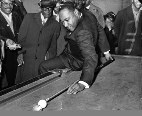 "Civil rights leader Martin Luther King Jr. tries for a behind-the-back shot, while using his ""best stick"" in a pool match with Chicago civil rights leader Al Raby while working on an anti-slum campaign in Chicago."