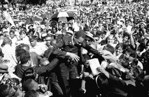 American civil rights leader Martin Luther King Jr. is helped through a massive crowd during a Chicago Freedom Movement rally in Grant Park in the 1960s.