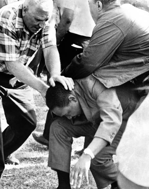 The Rev. Martin Luther King Jr. tries to regain his footing after being hit by a stone during an open housing march Aug. 5, 1966, but aides prevent him from rising to protect against further attacks.