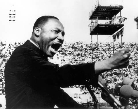 Martin Luther King Jr. speaks passionately in front of large crowd in 1964 at the Illinois Rally for Civil Rights at Soldier Field in Chicago. The rally was held to celebrate the passage of the 1964 Civil Rights Act.
