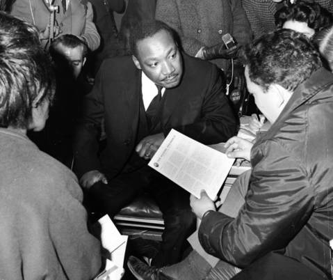 The Rev. Martin Luther King Jr., center, appears intense as he discusses fair housing with Gilbert Balin, of G. Balin Inc. real estate agents in Chicago on Nov. 3, 1966.