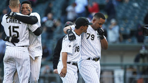 Jose Abreu heads to the dugout with teammate Tyler Saladino after hitting the game-winning single in the 11th inning to beat the Rangers 4-3 at U.S. Cellular Field on April 23, 2016.