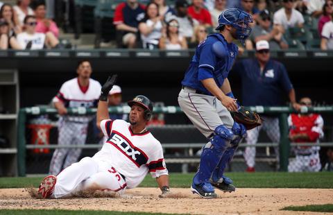 Jose Abreu scores behind Rangers catcher Brett Nicholas in the eighth inning on April 24, 2016 at U.S. Cellular Field.
