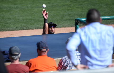Jose Abreu tosses a ball to a fan between innings of a spring training game against the Brewers at Camelback Ranch on March 8, 2016.