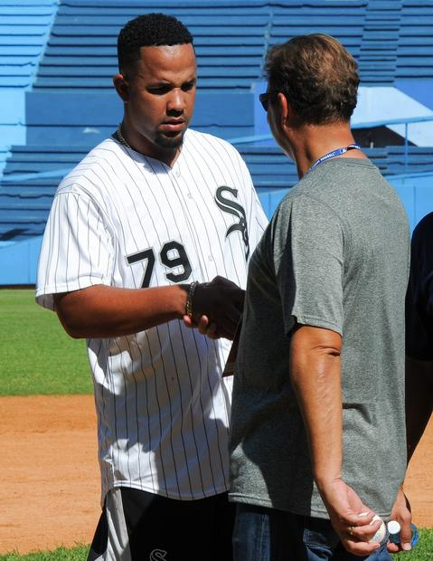 Jose Abreu shakes hands with former Cuban President Fidel Castro's son, Antonio Castro, during a children baseball training session at the Latin American Stadium in Havana on Dec. 16, 2015.