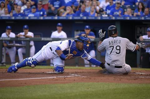 Jose Abreu slides past Royals catcher Salvador Perez as he scores in the first inning at Kauffman Stadium.