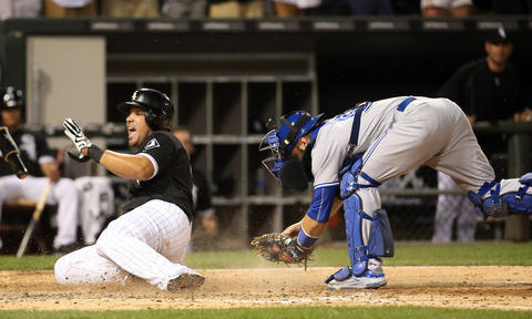 Jose Abreu slides into home plate ahead of a tag by Blue Jays catcher Russell Martin to score in the eighth inning.