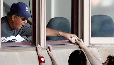 Fan favorite Ron Santo signs autographs between innings from the radio booth during spring training as the Chicago Cubs host the Milwuakee Brewers at HoHoKam Park, in Mesa, Arizona.