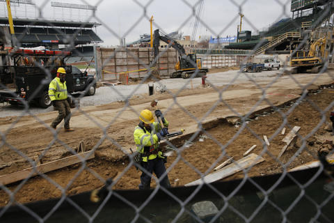 Construction crew members work on infrastructure on North Sheffield Avenue on Nov. 26, 2014, outside the right field bleachers at Wrigley Field in Chicago.