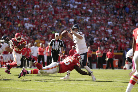 Jay Cutler throws the game-winning touchdown pass to running back Matt Forte while under pressure from Chiefs defensive lineman Jaye Howard late in the fourth quarter.