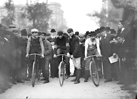 Cyclists J. E. Gill, C.A. Linde and Ed Bukowski, position their bicycles in front of a crowd on North Michigan Avenue in Chicago in 1901.