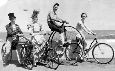 """These bicycles, as well as many other wheels of every vintage, took part in a huge parade of more than 6,000 cyclists celebrating Bicycle Day at the Chicago World's Fair on Aug. 21, 1934. Other events scheduled were a team relay race for the American Championship, a five-mile race and a race for old-time bike champions. Left to right are Robert Van Deventer, Helen Trudel and Allen Blair of the cast of """"Wings of a Century"""" and Louise Lindsay of the Cycle Trades of America exhibit."""