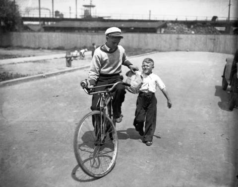 Edward Schmidt hands endurance bike rider George Hoffman a paper bag while Hoffman rode on the 4900 block of S. Artesian Ave., in Chicago's Gage Park neighborhood, in1930.
