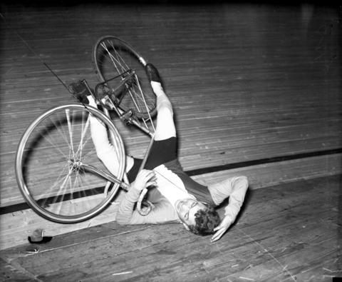 """Eddie Trieste, a six-day bike racer from the South Side of Chicago, takes a spill during the 31st International Chicago Six-Day Bike Race that started on March 11, 1934. """"There were six spills during the first two hours of the race,"""" the Tribune reported. """"None of the thrills of bike racing was missing for the opening night's customers. The crowd of 10,500 was almost a recordbreaker."""""""