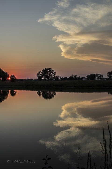After an active stormy day, the skies clear and I'm treated to this gorgeous sunset at the Fermilab in Warrenville, IL. The clarity of the reflection in a small pond was gorgeous.