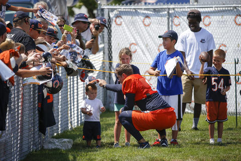 Jay Cutler puts a hat on a child after signing his hat on the first day of training camp at Olivet Nazarene University in Bourbonnais on July 28, 2016.