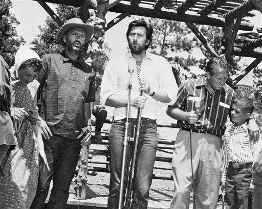 In this July 1955 photo released by Disney, Fess Parker, center, and Buddy Ebsen, left, rehearse for the opening day telecast of Disneyland in Anaheim, ...