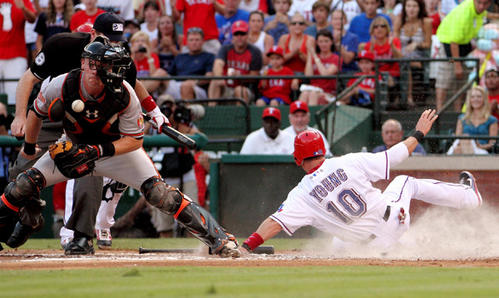 Texas Rangers designated hitter Michael Young (10) slides home safely as Baltimore Orioles catcher Matt Wieters (left) bobbles the throw during the second inning at Rangers Ballpark.