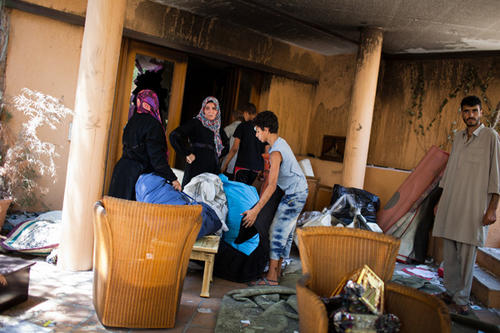People gather articles collected from inside a house at Baba al Azizia, Muammar Gaddafi's main military compound on August 27, 2011 in Tripoli, Libya.