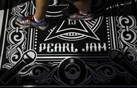 A fan walks on a Pearl Jam designed floor covering while attending the band's 20th anniversary tour at Alpine Valley in East Troy, Wisconsin, on Saturday, September 3, 2011.