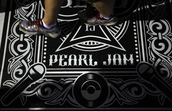 A fan walks on a Pearl Jam designed floor cover