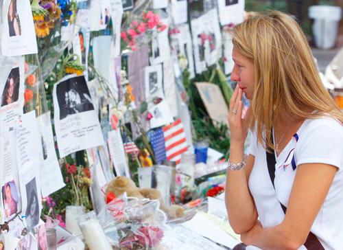A woman looks at posters listing the missing at a memorial in Union Square in New York one week after 9/11.