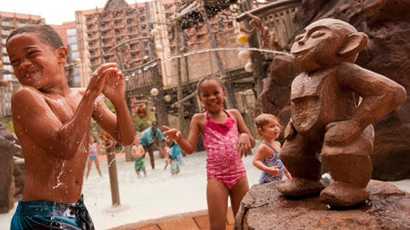 Children play in the Menehune Bridge water play structure at Disney's Aulani hotel in Hawaii.