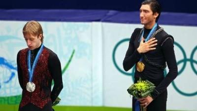 Evan Lysacek as the National Anthem is played at the 2010 Olympics, after he beat defending champion Evgeny Plushenko of Russia (L) for gold.  (Cameron Spencer / Getty Images)
