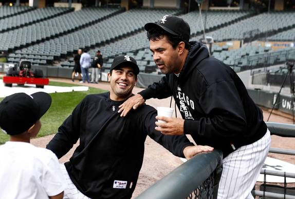 Ozzie Guillen talks with a kid and Chicago White Sox right fielder Carlos Quentin before the start of the game against the Toronto Blue Jays at U.S. Cellular Field.