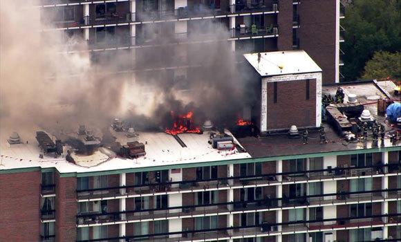 Firefighters battle a blaze on the roof of a high-rise building at 5901 N. Sheridan Rd.