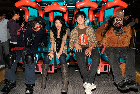 """Wizards of Waverly Place"" co-stars Selena Gomez and David Henrie climb aboard the Silver Bullet roller coaster with a few Wild West monsters during Halloween Haunt at Knott's Berry Farm."