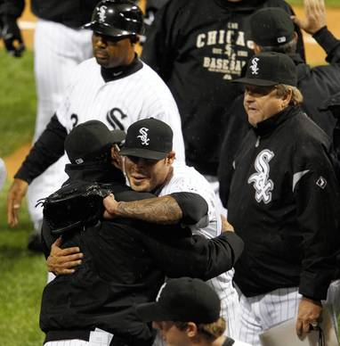 Ozzie Guillen gets a hug from Sergio Santos at the end of their 4-3 win over the Blue Jays.