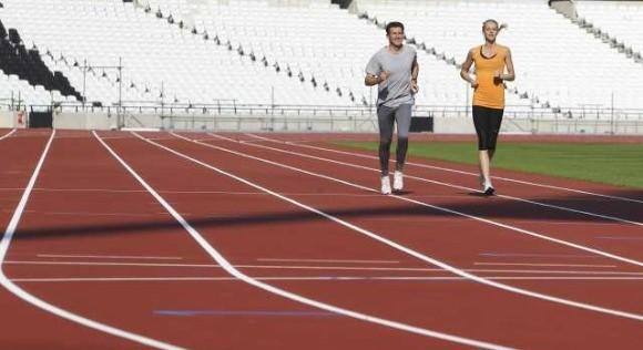 Two-time Olympic metric mile champion chairman Seb Coe, the London 2012 chairman, and 2011 world silver medalist Hannah England try out the new track at the 2012 Olympic Stadium last month. (Reuters)