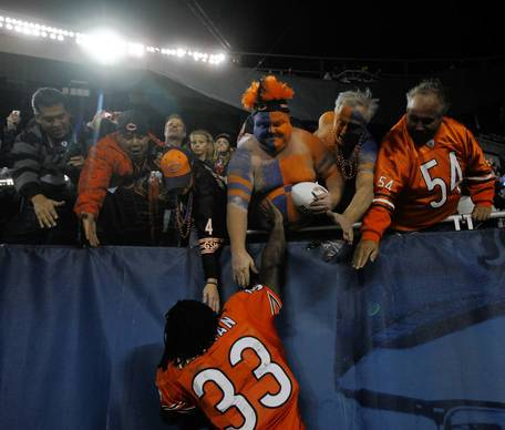 Charles Tillman stops to rub the belly of Bears fan Mike Lyp after the Bears' 37-13 win.