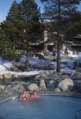Snowy pines and a steaming hot tub make magic at the Resort at Squaw Creek, California.